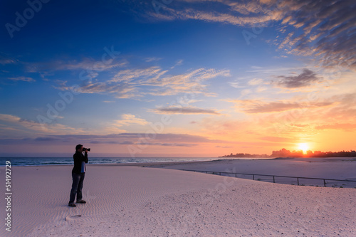 man takes a photograph of sunrise