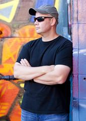 Man leaning on grafitti wall