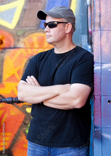 Man leaning on grafitti wall