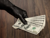 Human hand in black glove holding dollars