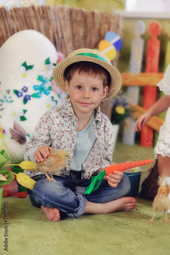 it's a wonderful boy in a straw hat with a chicken and carrots