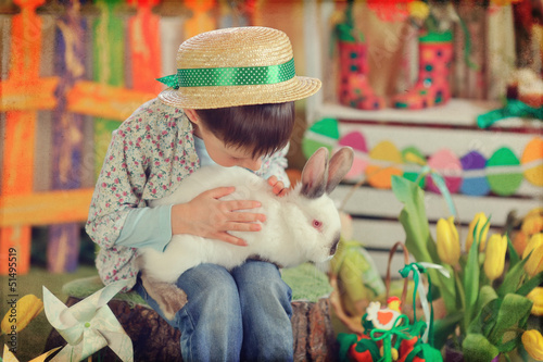 Easter theme with small boy with  bunnies, chicks and eggs