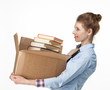 Smiling woman carrying a cardboard box with books
