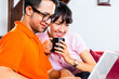 Asian couple on the couch with a laptop