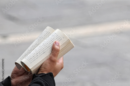 Male hands holding a japanese book