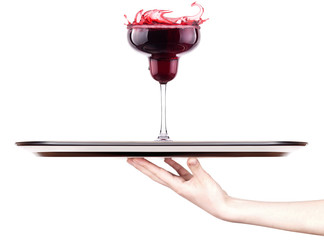 Red cocktail with splash on a tray with hand
