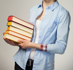Unrecognizable girl holding a stack of books; grey background