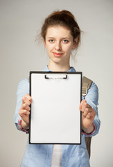 Attractive girl holding clipboard with blank sheet of paper