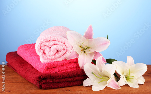 stack of towels with pink lily on blue background.