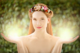 Beautiful fairy woman with glow in hands on natural green backgr