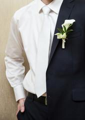 Bridegroom slips a coat over his shoulder, wedding day