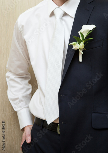 Bridegroom slips a coat over his shoulder, wedding day