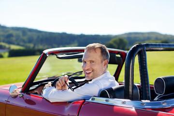 glücklicher mann im cabrio