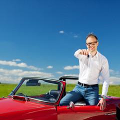 mann im cabrio zeigt schlüssel