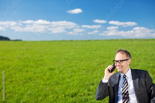 geschäftsmann telefoniert auf der grünen wiese