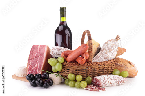 wicker basket with sausages, ham and wine