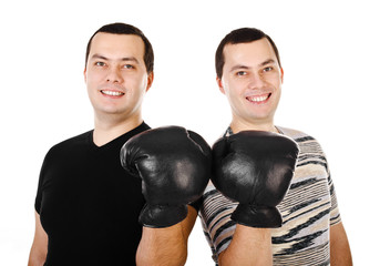 Two attractive smiling young men twins in boxing gloves isolated