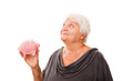 Portrait of a happy mature woman holding piggy bank isolated aga