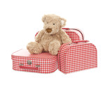 three vintage red and white suitcases with teddy bear