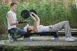 Detaily fotografie woman exercising with  barbell,man helping her