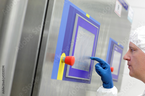 technician in  blue gloves touching screen at control panel