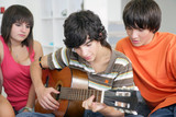 Teens listening to their peer play the guitar