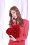 Frau mit Liebeskummer hält rotes Herz - sad woman with heart
