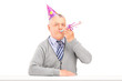 A happy birthday mature man with party hat blowing