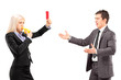 Woman in business suit showing a red card and blowing a whistle