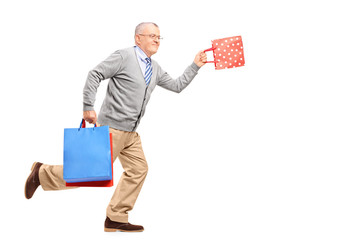 Full length portrait of a mature gentleman running with shopping