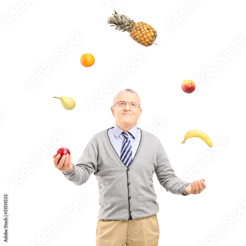 A mature man juggling fruits