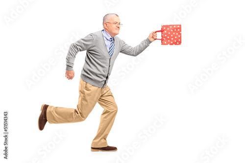 Full length portrait of a mature gentleman running with a gift b