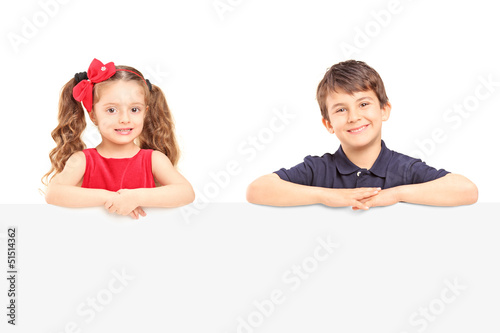 Little smiling boy and girl standing behind a blank panel