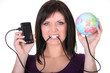 Woman frustrated at her phone plugged into a globe