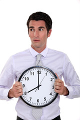 Businessman holding large clock