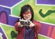 Style teen girl with camera standing near graffiti wall