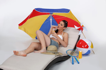 Brunette laying on lounger drinking cocktail