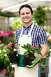 Employee in the greenhouse holding a vase