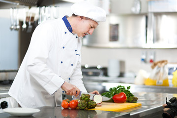 Chef cutting vegetables in a restaurant's kitchen