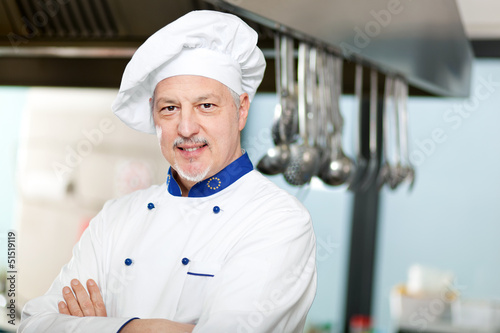 Male chef with arms crossed in restaurant kitchen