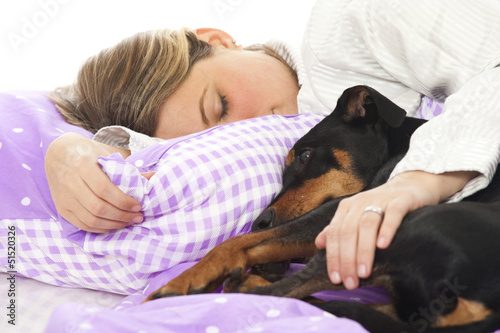 Young woman lying in bed with dog