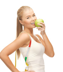 sporty woman with apple and measuring tape