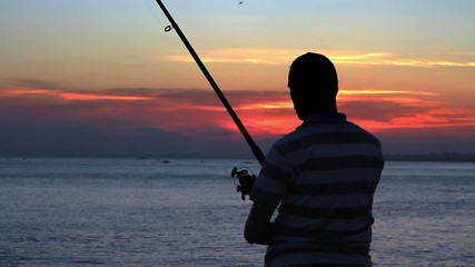 Fisherman throws a fishing tackle against sunset