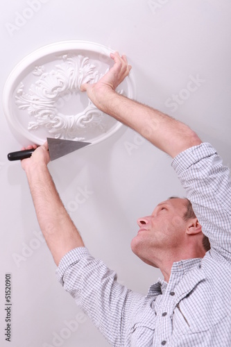Decorator affixing a ceiling rose