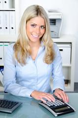 sekretärin mit taschenrechner lächelt in die kamera