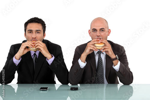 Two businessmen enjoying a burger.