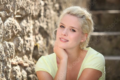 Blonde woman next to stone wall