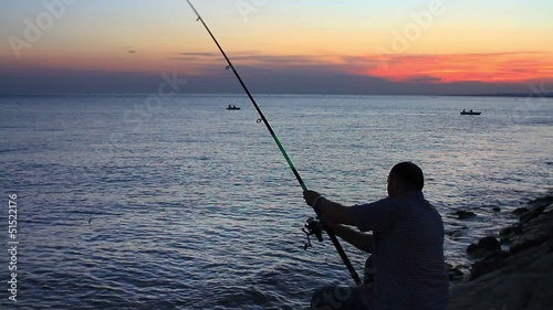 Fisherman with fishing tackle and catching fish