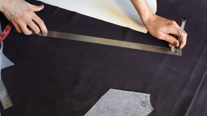 girl draws a line on the fabric