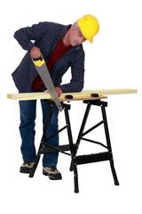 Tradesman sawing a plank